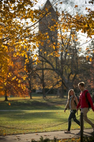 two students walking on central campus with campanile in the background and yellow fall leaves in the foreground