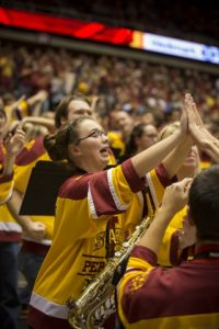 A member of the marching band holding a saxophone high fives other students at a sporting event in Hilton Coliseum