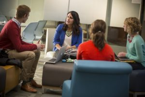 Three students sit with an advisor in a lounge area on campus.