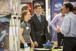 Two students dressed in business attire talk to an employer at a career fair