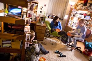 Three girls sit around in a dorm room at Iowa State.