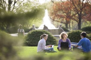 Three students with laptops sit in the grass with the Memorial Union fountain in the background.