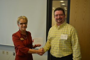 Dr. Kristen Constant gifts an outgoing EAC member with a card and handshake.