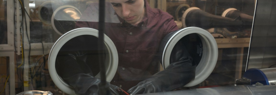 Materials Engineering student, Sean Russell, does work inside of a glove box.