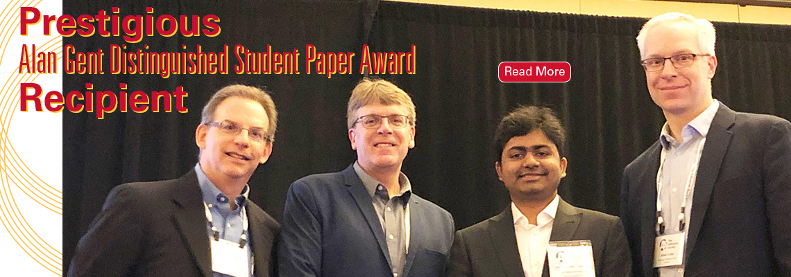 Image text: Prestigious Alan Gent Distinguished Student Paper Award Recipient. Image shows four men standing together at an awards ceremony